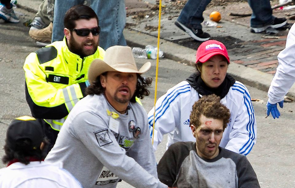**EDITORS NOTE: GRAPHIC CONTENT** First responders including Carlos Arredondo, in cowboy hat, tend to Jeff Bauman, who was se