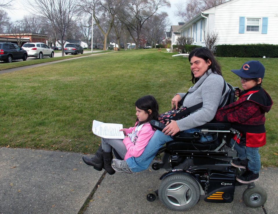 In this Nov. 19, 2012 photo, twins Abigail and Noah Thomas, 8, ride on the motorized wheelchair of their mother, Jenn Thomas,