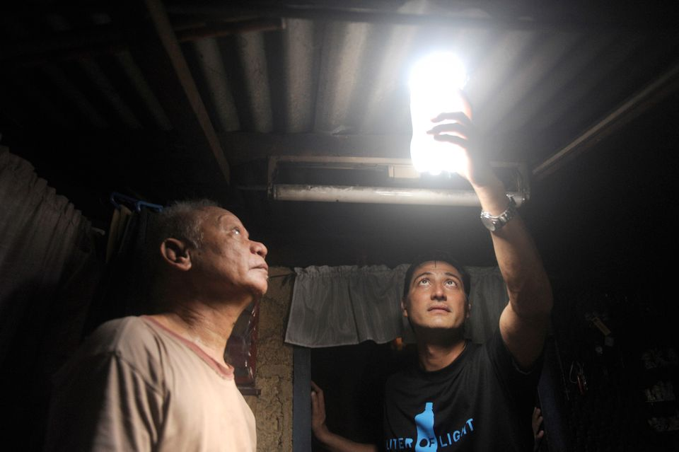Illac Diaz (R) inspects a solar light bulb with Siplicio Mondas, 73, installed by the Philippine army soldiers on a roof in a