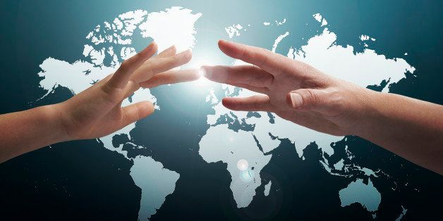 Female adult and 9yrs old boy's hands touch across the world