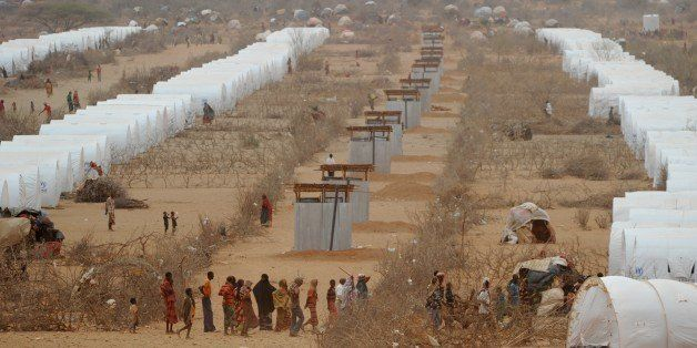 Somali refugees line up to receive aid near a row of tents they now call home at the Kobe refugee camp near the Ethiopia-Soma