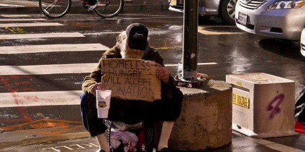 SAN FRANCISCO, CA - DECEMBER 22: A panhandler begs for money at the entrance to Macy's Union Square on December 22, 2012, in