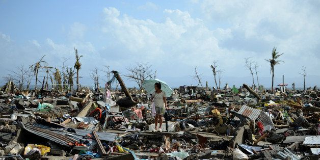 A surivor walks among the debris of houses destroyed by Super Typhoon Haiyan in Tacloban in the eastern Philippine island of