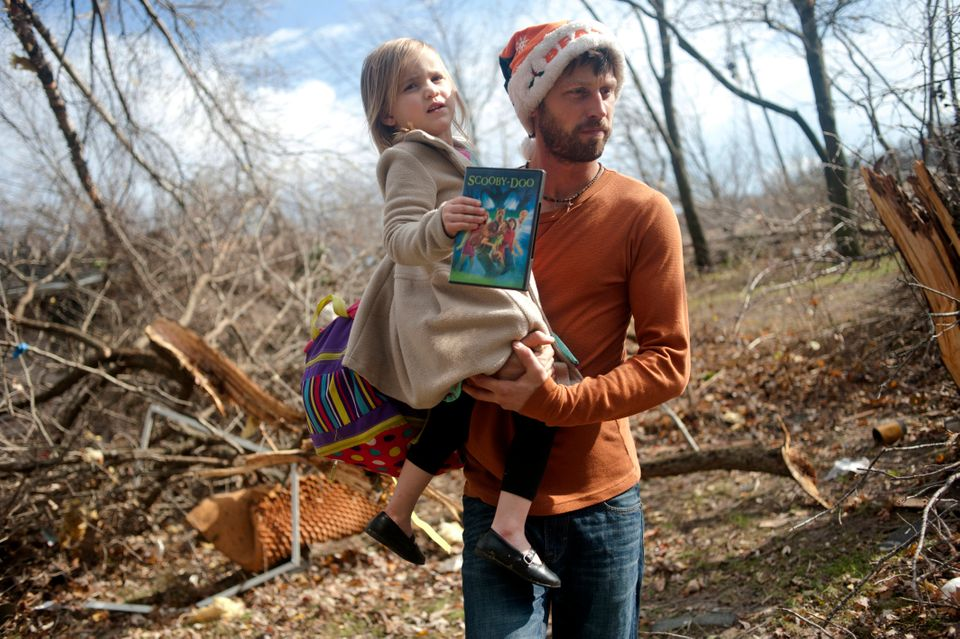 East Peoria resident Billy Vestal evacuates with his daughter, Lillian Vestal, 3, after a tornado damaged the area near Chest