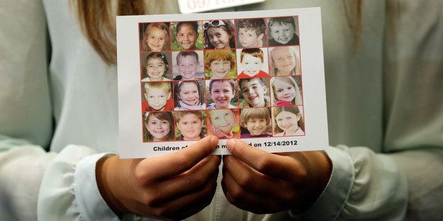 WASHINGTON, DC - SEPTEMBER 18:  Kyra Murray holds a photo with victims of the shooting at Sandy Hook Elementary School during
