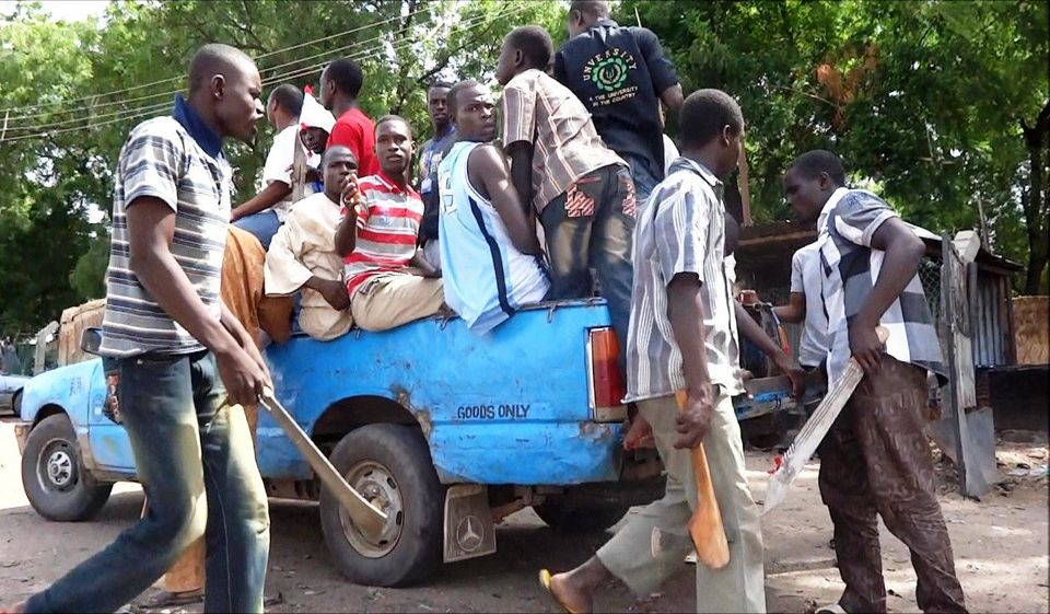 Machete and axe-wielding neighborhood vigilantes hop into a truck on July 19, 2013, for an operation to hunt down Boko Haram
