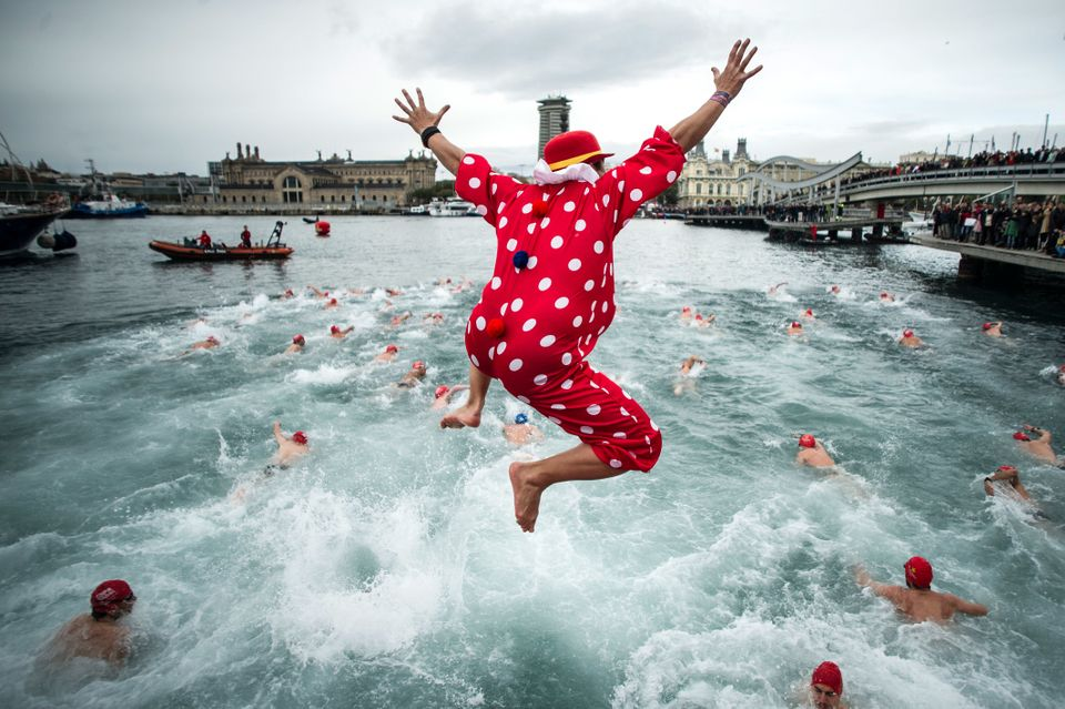 BARCELONA, SPAIN - DECEMBER 25:  A competitor in Christmas fancy dress jumps into the sea during the 104rd Barcelona Traditio
