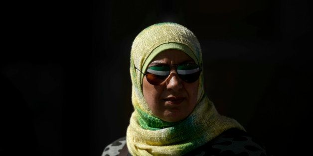 The Syrian National Coalition flag is reflected in a woman's sunglasses during a rally against Syrian President Bashar al-Ass