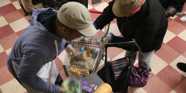 NEW YORK, NY - DECEMBER 11:  Harlem residents pack free groceries at the Food Bank For New York City on December 11, 2013 in
