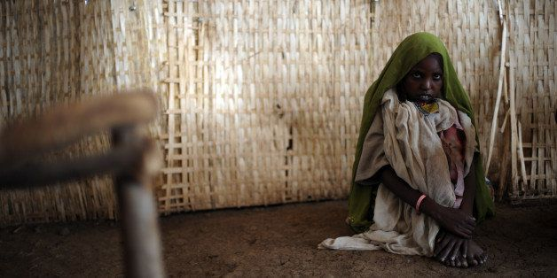 A young woman sits on the floor as she waits to receive medical help at the outpatient unit of a medical center run by Médeci