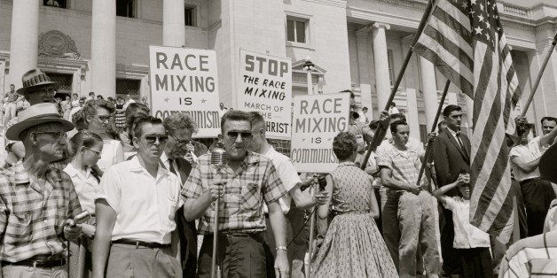 UNITED STATES - CIRCA 1959:  people holding signs and American flags protesting the admission of the 'Little Rock Nine' to Ce