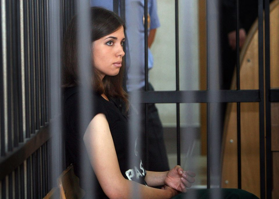 Nadezhda Tolokonnikova, a member of the feminist punk band, Pussy Riot, listens from behind bars at a district court in Saran