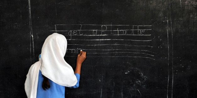 A Pakistani female student writes a sentence on a black board at a government school in Peshawar on October 25, 2012. AFP PHOTO/A. MAJEED (Photo credit should read A. MAJEED/AFP/Getty Images)