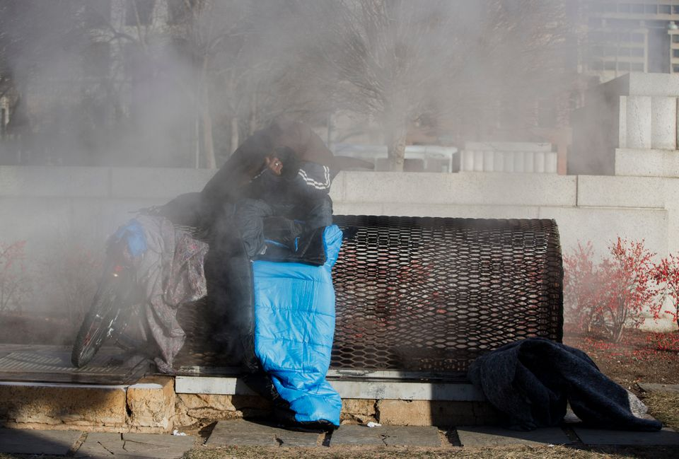 A homeless man who wanted to be identified as John, tries to stay warm on a steam grate in Washington.