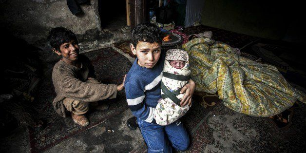 A Syrian refugee boy poses with his newborn brother as their mother lies near them in a house in the Basaksehir district of I