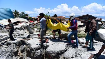 Villagers carry the body of a victim following earthquakes and tsunami in Palu Central Sulawesi Indonesia