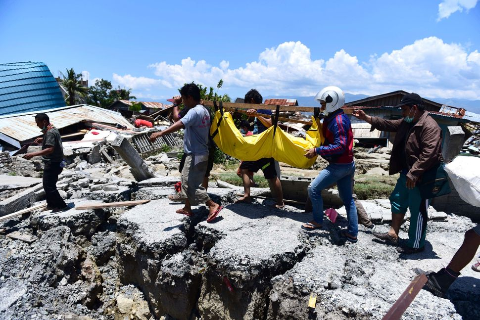 Villagers carry the body of a victim following earthquakes and a tsunami in Palu, Central Sulawesi, Indonesia.<i></i><i></i>