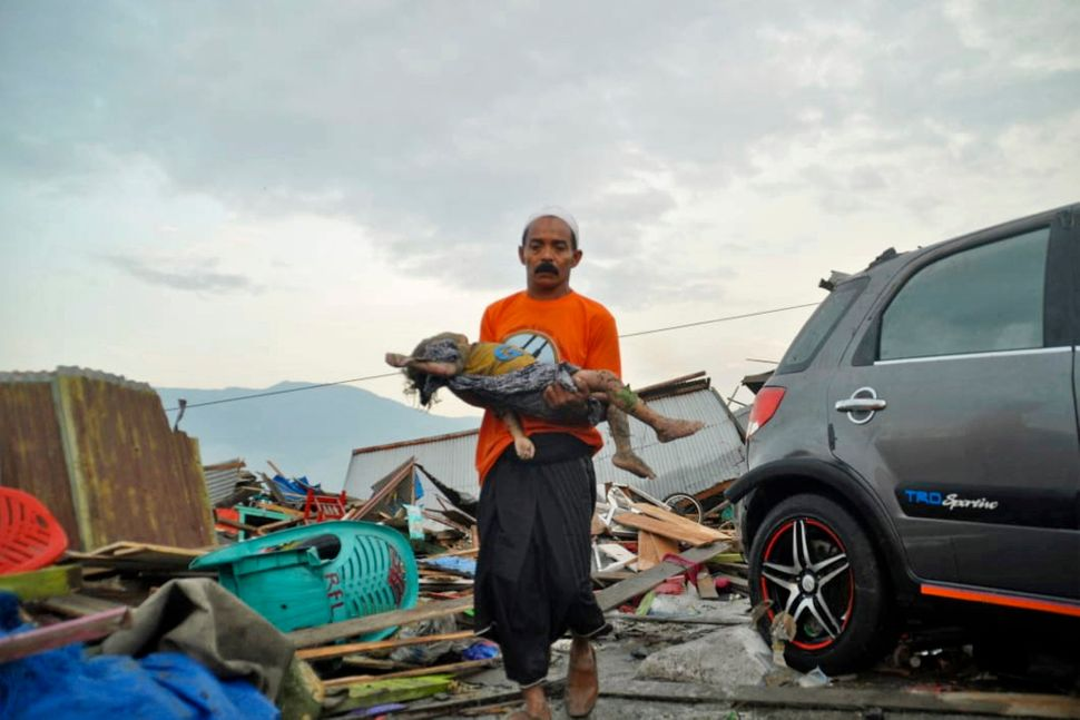 A man carries the body of a child who was killed in the tsunami in Palu.<i></i><i></i>