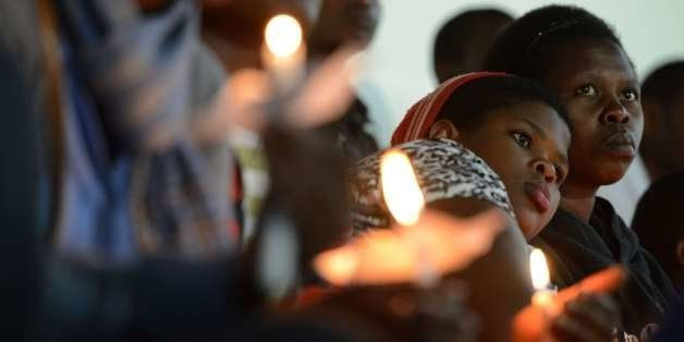 Rwandan women hold candles during a night vigil and prayer for genocide victims at the Amahoro stadium in Kigali, Rwanda, on