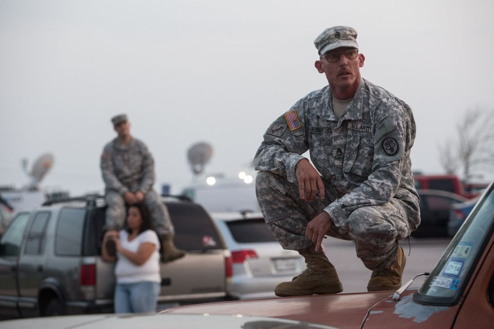 Staff Sgt. John Robertson, right, waits in a parking lot outside of the Fort Hood military base for updates about the shootin