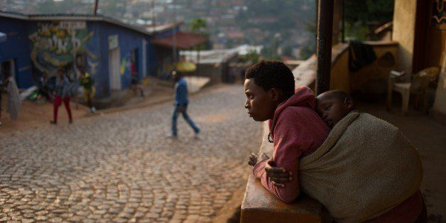 A woman stands on her porch at a suburb set on a hill overlooking Kigali, on March 13, 2014. Twenty years after the genocide
