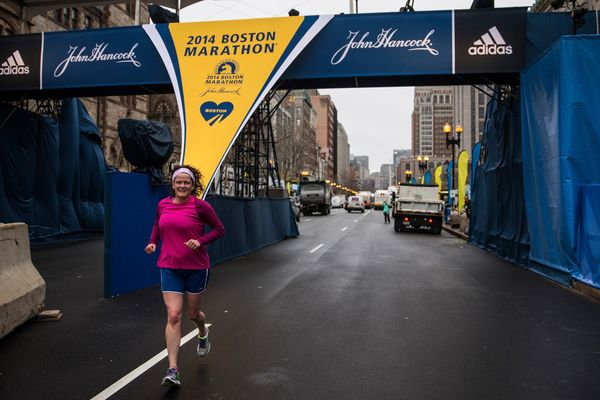 A runner runs underneath the Boston Marathon finish line photo bridge on the morning of the one-year anniversary