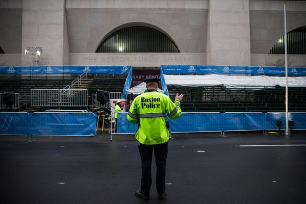 A Boston police officer waves traffic across the finish line of the Boston Marathon on the one-year anniversary.