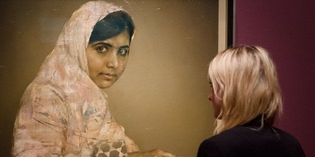 A gallery worker poses with a painted portrait of Malala Yousafzai, the teenage Pakistani advocate for girls education who wa