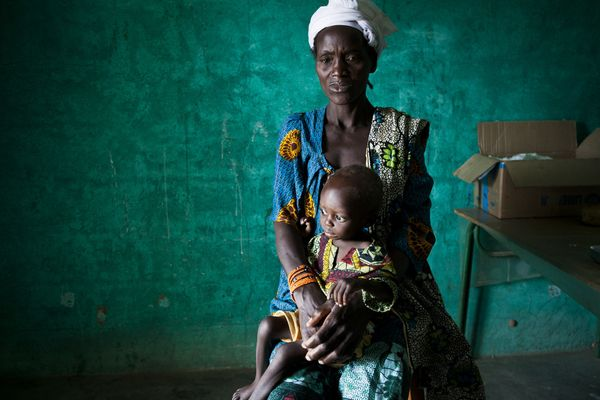 Awa waits at a health post with her son Modiba, two, for medication to treat severe malnutrition and malaria in Sakasso Regio