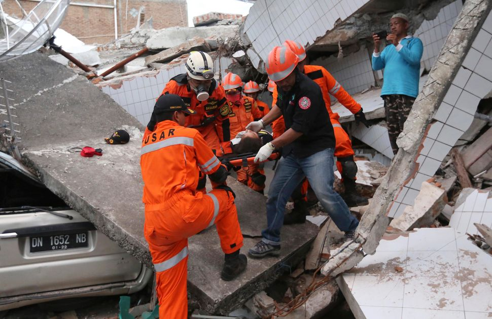 Rescuers pulled a survivor&nbsp;from a building damaged by a massive earthquake in Palu.<i></i><i></i>