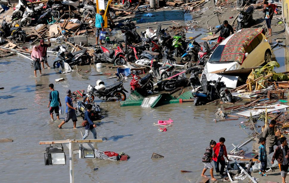 People survey a flooded shopping mall that was damaged in the earthquake and tsunami on Friday.<i></i><i></i>