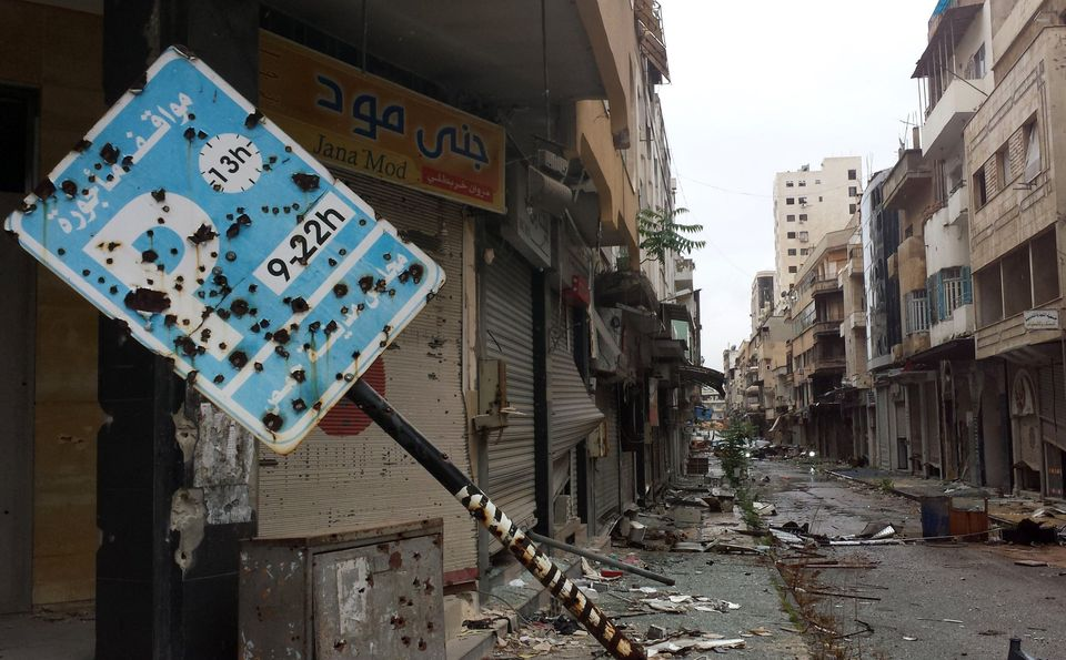 A bullet-riddled parking sign stands amid debris in a deserted street  leading into the old city of Homs on May 8, 2014. (YOU