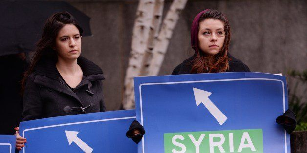 Women hold signs representing highway signs leading United Nations trucks with humanitarian aid to Syrian April 30, 2014 duri