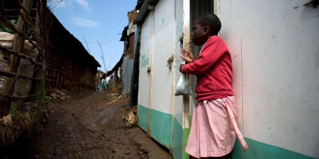 A young school girl emerges from a latrine holding a used Pee Poople bag on June 8, 2012 at Kibera slum, in the Kenyan capita