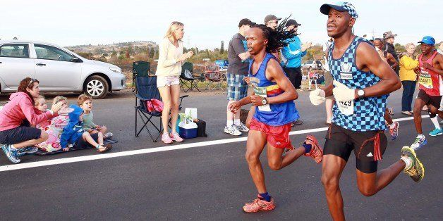 Spectators cheer runners as close to 16, 000 competitors from South Africa and abroad run the 89,2 kilometres ultra distance Comrades Marathon from Pietermaritzburg to Durban on June 1, 2014. AFP /PHOTO RAJESH JANTILAL (Photo credit should read RAJESH JANTILAL/AFP/Getty Images)