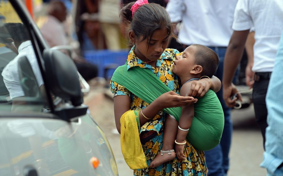 An Indian youth carrying a toddler counts money collected by begging from commuters at a busy traffic intersection on the eve