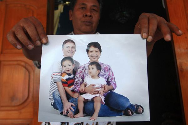 Widi Yuwono, the brother of Yuli Hastini, right, shows her sister's family portrait with her Dutch husband John Paulissen and