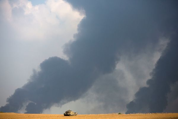 An Israeli tank sits in a field as heavy smoke rises from the Gaza Strip Tuesday, July 22, 2014. Israeli airstrikes pummeled