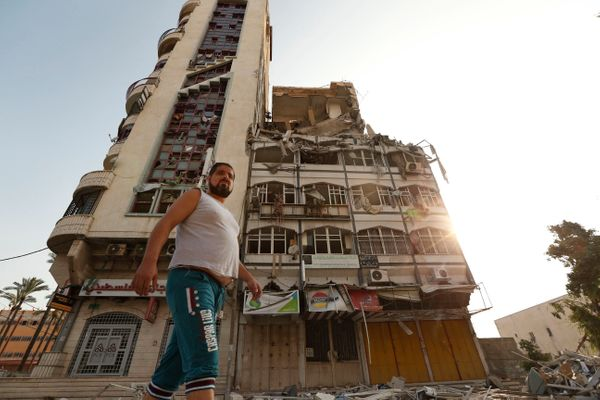 Palestinians inspect the damage of the Al-Shalam (Peace) tower, destroyed by an overnight Israeli strike, in Gaza City, Tuesd