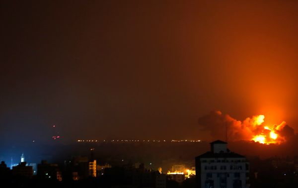 Flames spread across buildings after Israeli strikes in the Shijaiyah neighbourhood in Gaza City, Tuesday, July 22, 2014. A h