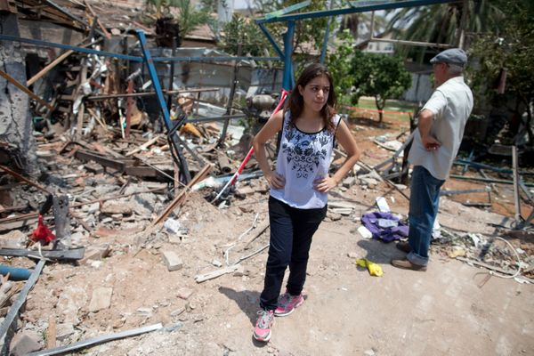 YAHUD, ISRAEL - JULY 22: (ISRAEL OUT) An Israeli woman inspects an Israeli home allegedly hit by a Hamas rocket  on July 22,
