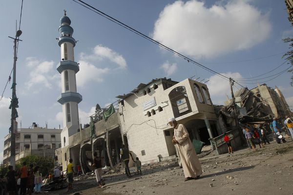 Palestinians gather outside a partly destroyed mosque,  following an overnight Israeli military strike, on July 22, 2014 in R