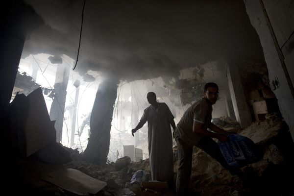 Palestinian men remove goods from the rubble of a destroyed store located on the ground floor of a building hit by an Israeli