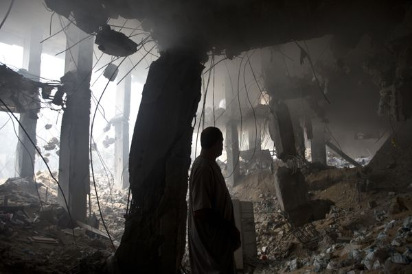 A Palestinian man inspects the rubble of a destroyed store located on the ground floor of a building hit by an Israeli air st