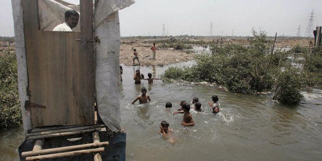 MUMBAI, INDIA:  A slum resident uses a toilet that opens into the water below as children swim in the water near a protest ra