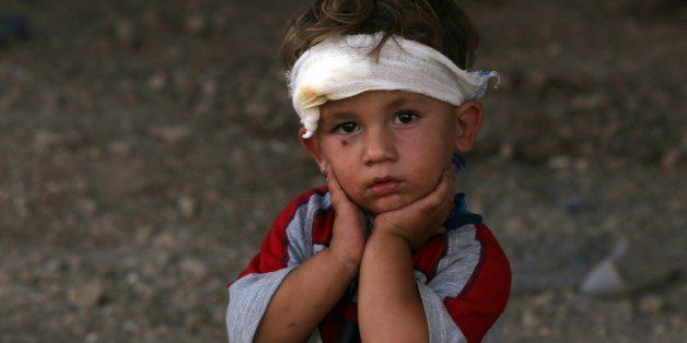 An Iraqi Yazidi child, whose family fled their home a week ago when Islamic State (IS) militants attacked the town of Sinjar, looks on at a makeshift shelter on August 10, 2014 in the Kurdish city of Dohuk in Iraq's autonomous Kurdistan region. 'The Kurdish peshmerga forces have succeeded in making 30,000 Yazidis who fled Mount Sinjar, most of them women and children, cross into Syria and return to Kurdistan,' said Shawkat Barbahari, a Kurdhish official who is in charge of the Fishkhabur crossing with Syria. AFP PHOTO/AHMAD AL-RUBAYE (Photo credit should read AHMAD AL-RUBAYE/AFP/Getty Images)