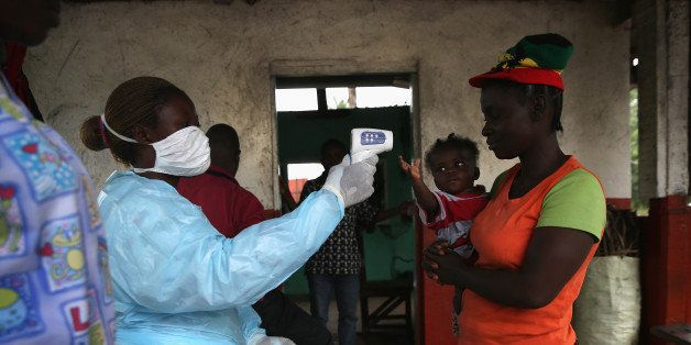 DOLO TOWN, LIBERIA - AUGUST 24:  A Liberian Ministry of Health worker checks people for Ebola symptoms at a checkpoint near t