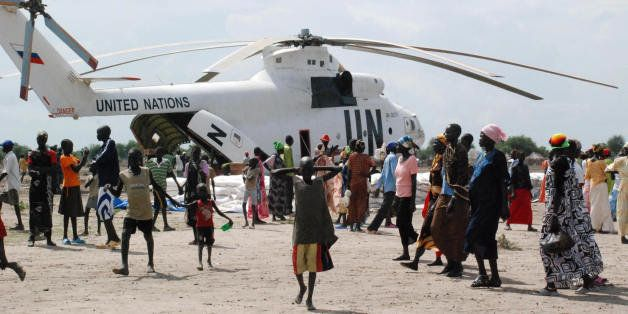 TO GO WITH AFP STORY BY PETER MARTELL Food aid is offloaded from a United Nations helicopter in the southern Sudanese town of