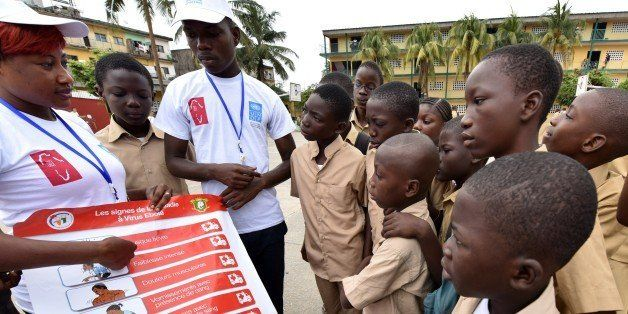 Volunteers wearing t-shirts of the United Nations Development Programme (UNDP) show a placard to raise awareness on the sympt