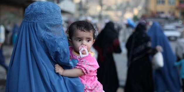 A woman wearing a burqa carries a child through the old town area of Kabul on June 19, 2010. At least five civilians, includi